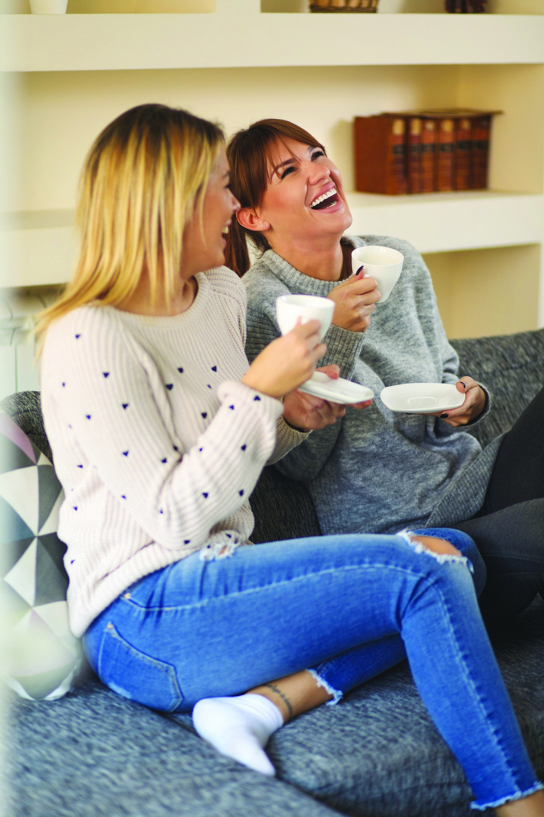 Two young cheerful female friends that are spending time together at home, enjoying drinking coffee and having good conversation