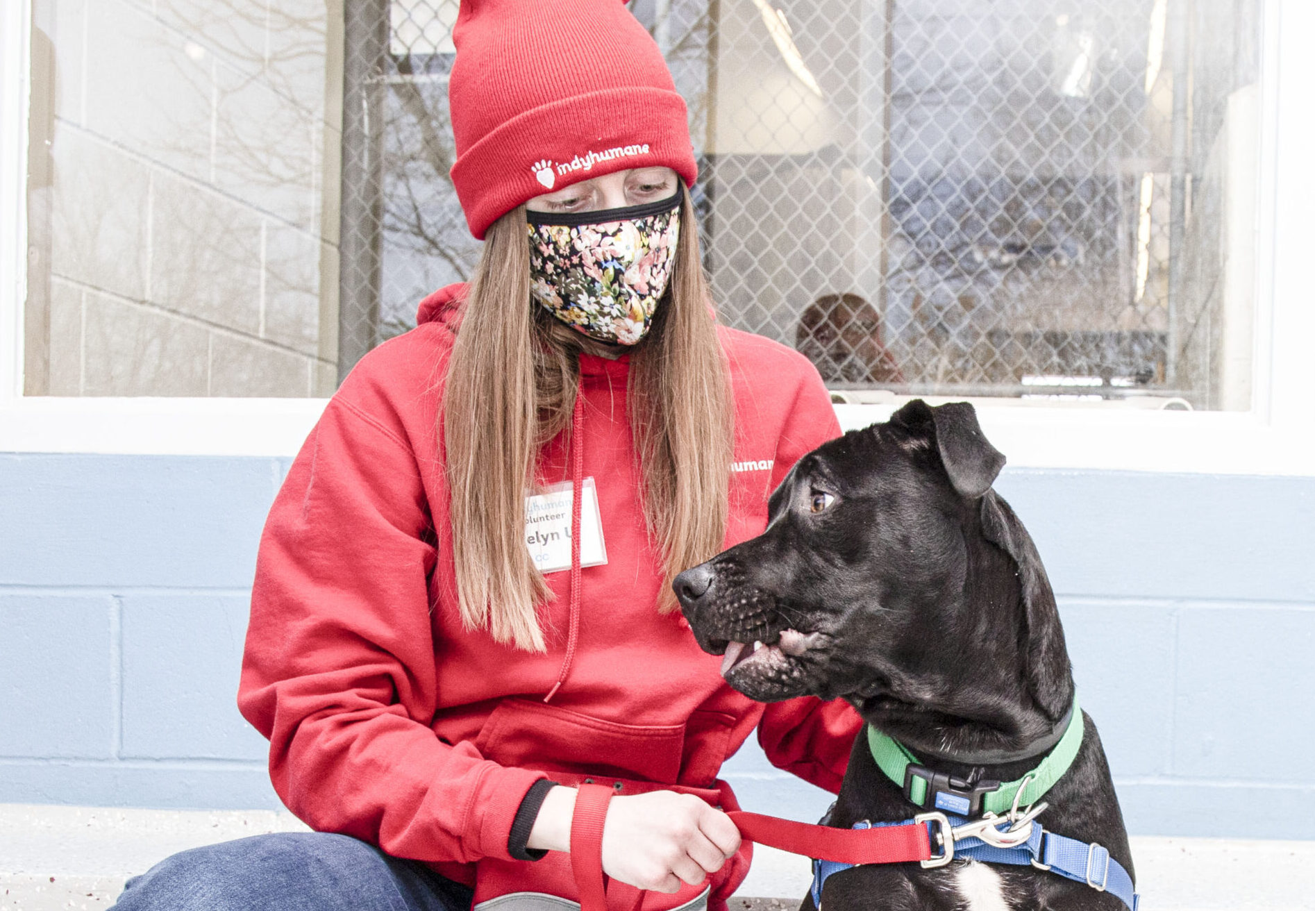 A girl in a red suit with a rad hat sitting outside with a black dog looking to the right